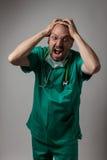 Porträt eines jungen Arztschreiens Stockbild