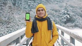 Porträt eines jungen attraktiven Mannes in der Winterkleidung, die Smartphone mit dem grünen Schirm untersucht die Kamera zeigt stock video