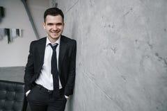 Porträt eines jungen attraktiven Mannes in einem schwarzen Anzug und der Bindung mit einem Lächeln und einem überzeugten Blick Stockbilder