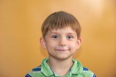 Porträt eines Jungen auf einem beige Hintergrund, ein frohes Kind untersucht die Kamera stockbild
