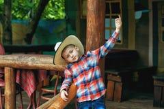 Porträt eines Jungen auf einem Weg in einem breitrandigen Hut lizenzfreie stockbilder