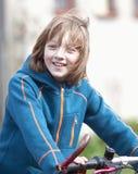 Porträt eines Jungen auf Fahrrad Stockbild