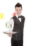 Porträt eines jungen Butlers oder des Bediensteten mit Gläsern Champagner Lizenzfreie Stockbilder