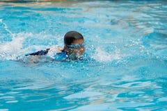 Porträt eines Jungen, der öffentlich Swimmingpool spielt stockfotos