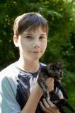 Porträt eines Jungen, der ein schwarzes Kätzchen hält Lizenzfreies Stockfoto