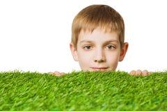 Porträt eines Jungen, der heraus durch Gras lugt Stockfotos