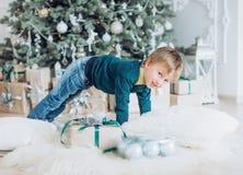 Porträt eines Jungen, der nahe dem Weihnachtsbaum spielt stockbilder