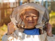 Porträt eines Jungen in der Schutzkleidung des Imkers Stockfotos