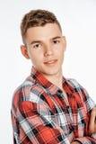 Porträt eines Jungen in einem Fotostudio Junger Mann, der auf einem weißen Hintergrund aufwirft lizenzfreies stockbild