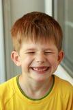 Porträt eines Jungen in einem gelben T-Shirt, dessen vordere Spitzenmilchzähne herausgefallen haben Stockbild
