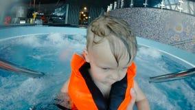 Porträt eines Jungen in einer Schwimmweste in einem Jacuzzi Langsame Bewegung 4K stock video