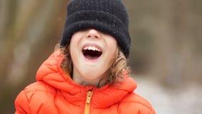 Porträt eines Jungen in einer Winterstrickmütze Seine Augen werden mit einem Hut, er lacht geschlossen stock video footage