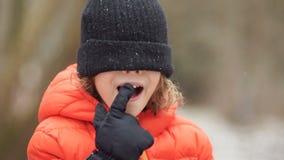 Porträt eines Jungen in einer Winterstrickmütze Seine Augen werden mit einem Hut, er schreit geschlossen stock video footage