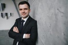 Porträt eines jungen erfolgreichen Mannes in einem schwarzen Anzug gegen eine graue Betonmauer in der Dachbodenart Lizenzfreies Stockbild
