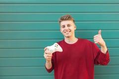 Porträt eines jungen Gamer, der mit einem Steuerknüppel in seiner Hand auf einem farbigen Hintergrund, Darstellen Daumen oben ste lizenzfreie stockbilder