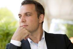 Porträt eines jungen Geschäftsmannes in einem dunklen Anzug und in einem weißen Hemd Lizenzfreies Stockbild