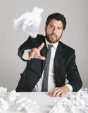 Porträt eines jungen Geschäftsmannes ermüdete und ein Papier werfend. Lizenzfreie Stockbilder