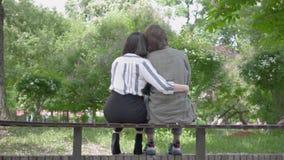 Porträt eines jungen glücklichen Paars in der zufälligen Kleidung Zeit im Park zusammen verbringend, ein Datum habend Liebhaber,  stock footage