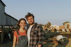 Porträt eines jungen glücklichen Paars an einem Bauernhof stockbilder