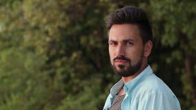 Porträt eines jungen gutaussehenden Mannes mit einem Bart Betrachten der Kamera stock video