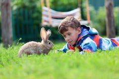 Porträt eines Jungen, hält er Kaninchen Stockfotos