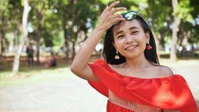 Porträt eines jungen indonesischen Mädchens in einem roten Kleid im Park stock video