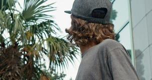 Porträt eines jungen Kerls, der an setzt und seine Kappe bei der Stellung in der Straße in der Zeitlupe entfernt stock video