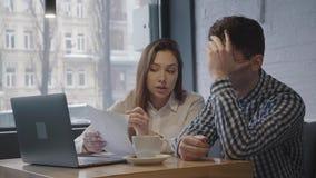 Porträt eines jungen Kerls und des Mädchens, die an einem Tisch mit einem Laptop nahe dem Fenster in einem gemütlichen Café sitze stock footage