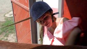Porträt eines jungen lächelnden Mädchens in einem Reitensturzhelm, ihr braunes junges Pferd kämmend 4K Video 4K stock footage