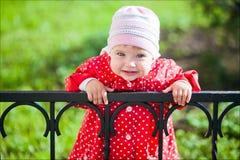 Porträt eines jungen lächelnden Mädchens in einem roten Mantel mit Tupfen stockbild