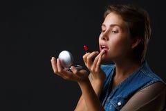 Porträt eines jungen Mädchens auf einem schwarzen Hintergrund, der ihre Lippen mit rotem Lippenstift malt stockbild