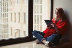 Porträt eines jungen Mädchens, das ein eBook am Fenster liest stockfoto