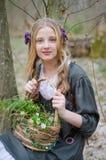 Porträt eines jungen Mädchens, das einen Korb von wilden Blumen hält stockfotografie