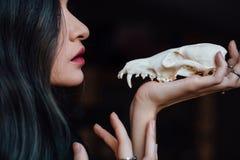 Porträt eines jungen Mädchens, das einen mysteriösen Schädel in den Händen eines Fuchses hält Gemaltes langes Haar Stockfotografie