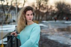Porträt eines jungen Mädchens, das wegholding an zu einem Zaun in der Straße schaut Lizenzfreie Stockfotos