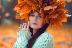 Porträt eines jungen Mädchens mit einem Ahornkranz auf ihrem Kopf in einem Herbstpark Lizenzfreie Stockbilder