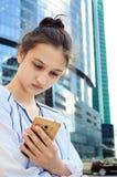 Porträt eines jungen Mädchens mit einem Handy, vertikale Fotografie lizenzfreie stockfotos