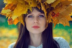 Porträt eines jungen Mädchens mit einem Kranz von Blättern auf ihrem Kopf in einem Herbstpark Lizenzfreies Stockfoto