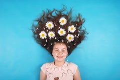 Porträt eines jungen Mädchens mit Gänseblümchen in ihrem Haar, das auf dem Boden liegt lizenzfreie stockfotos