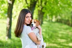 Porträt eines jungen Mädchens mit ihrem Hund im Park stockbilder