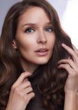 Porträt eines jungen Mädchens mit perfekter Haut und Make-up, mit dem gelockten dunklen Haar Lizenzfreies Stockfoto