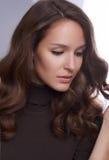 Porträt eines jungen Mädchens mit perfekter Haut und Make-up, mit dem gelockten dunklen Haar Stockbild