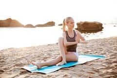 Porträt eines jungen Mädchens, welches das Ausdehnen tut, trainiert auf Strand Lizenzfreies Stockfoto