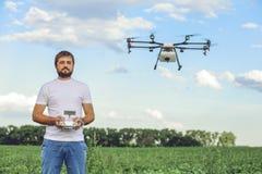 Porträt eines jungen männlichen Landwirts mit einem Berufsbrummen gegen ein grünes Feld Lizenzfreie Stockbilder
