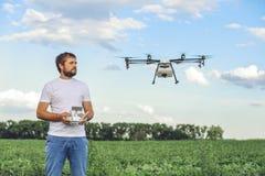 Porträt eines jungen männlichen Landwirts mit einem Berufsbrummen gegen ein grünes Feld Lizenzfreies Stockfoto