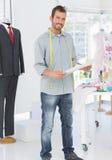 Porträt eines jungen männlichen Modedesigners, der Skizze hält Stockfotografie