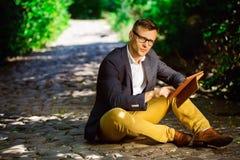 Porträt eines jungen Mannes in den Gläsern unter Verwendung einer Tablette Stockfoto