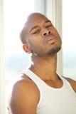 Porträt eines jungen Mannes, der durch Fenster sich entspannt Stockfoto