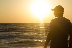 Porträt eines jungen Mannes in der Kappe auf dem Strand Stockfotografie