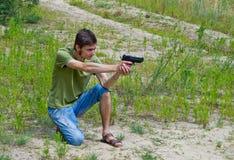 Porträt eines jungen Mannes, der mit einem Bolzenschussapparat zielt Stockbild